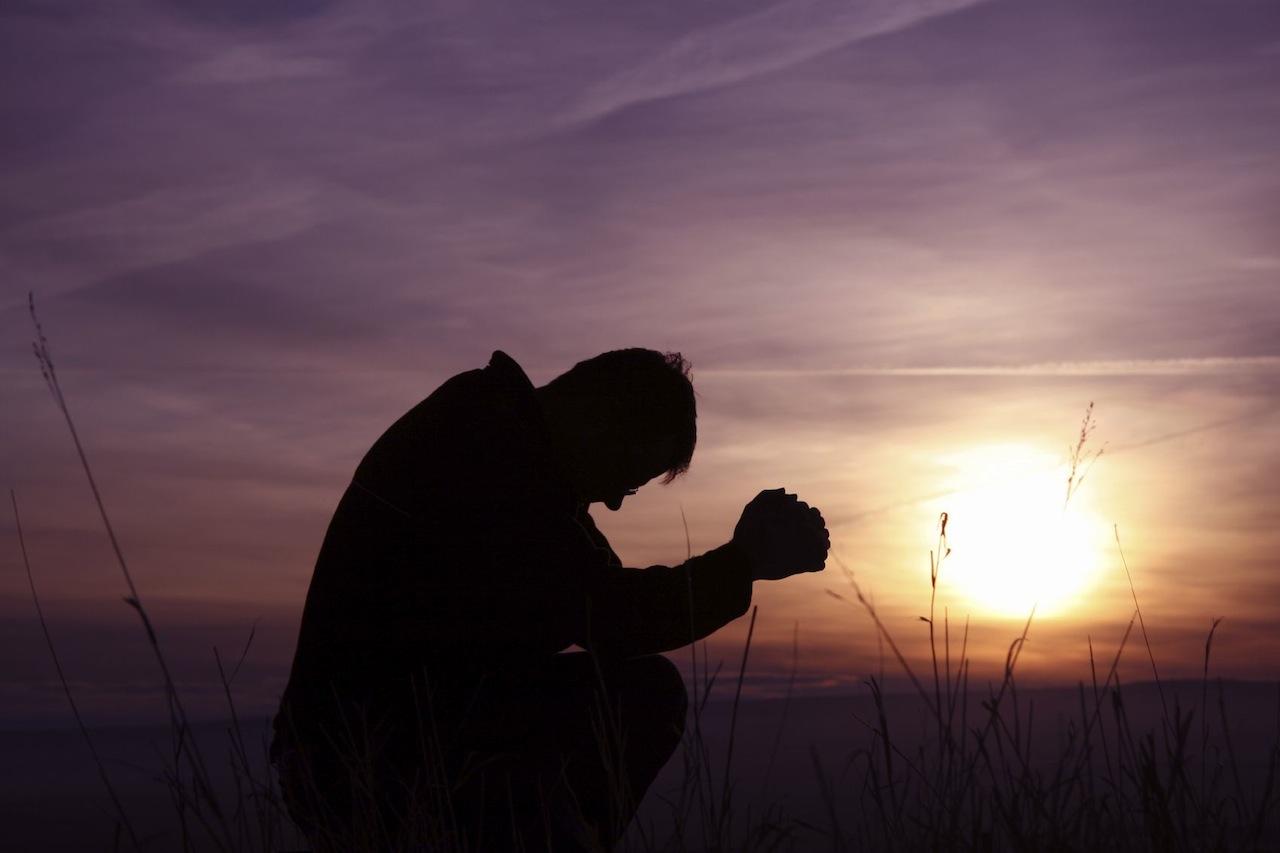 man-praying-silhouette-purple-sunset