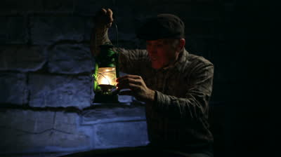 stock-footage-elderly-man-lighting-an-old-oil-lamp-in-darkness-and-leaving-the-frame