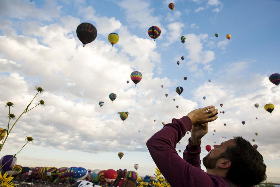 A man uses his phone to take pictures as hundreds of hot air balloons lift off on the first day, October 3, 2015. REUTERS/Lucas Jackson