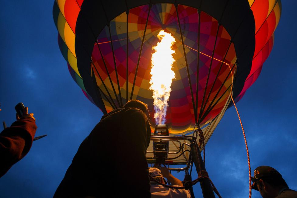 Attendees watch a hot air balloon gets lit by flames as it is being prepared for take off, October 4, 2015. REUTERS/Lucas Jackson