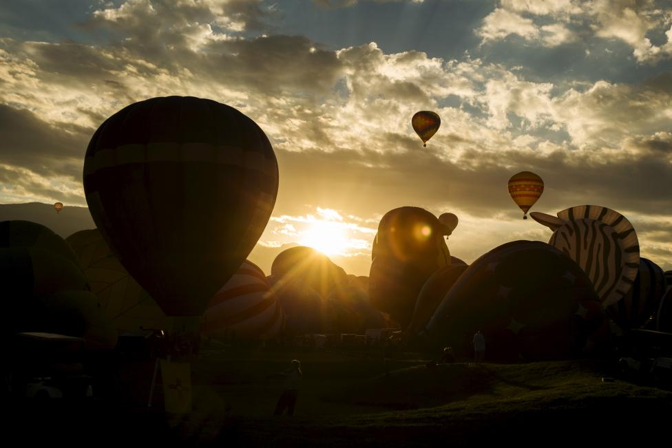 Hot air balloons lift off as the sun rises over the first day, October 3, 2015. REUTERS/Lucas Jackson