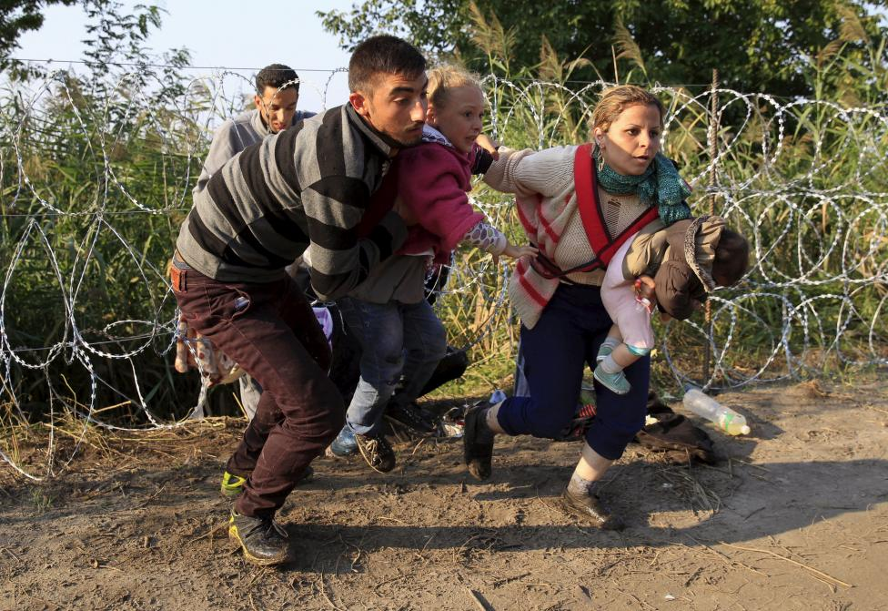 Syrian migrants run after crossing under a fence as they enter Hungary, at the border with Serbia, near Roszke, August 27, 2015. REUTERS/Bernadett Szabo