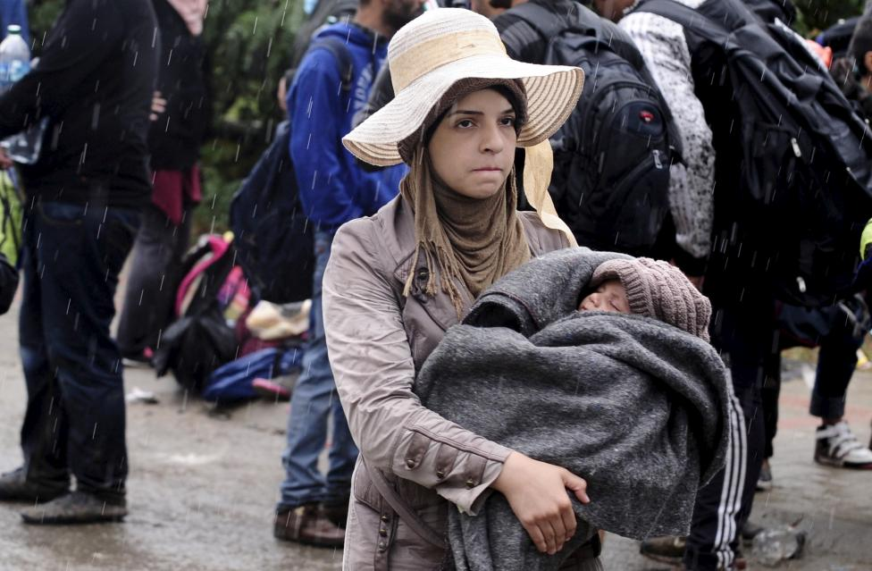 A migrant woman carrying a child waits in the rain at a transit camp near Gevgelija, Macedonia, after entering the country by crossing the border with Greece, September 10, 2015. REUTERS/Ognen Teofilovski