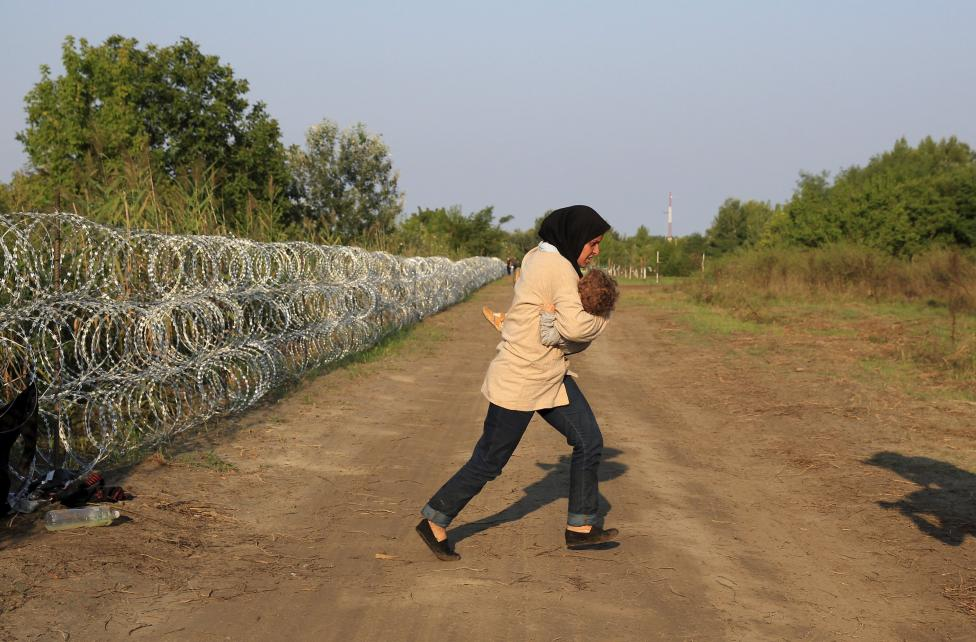A Syrian migrant runs after crossing under a fence as she enters Hungary, at the border with Serbia, near Roszke, August 27, 2015. REUTERS/Bernadett Szabo