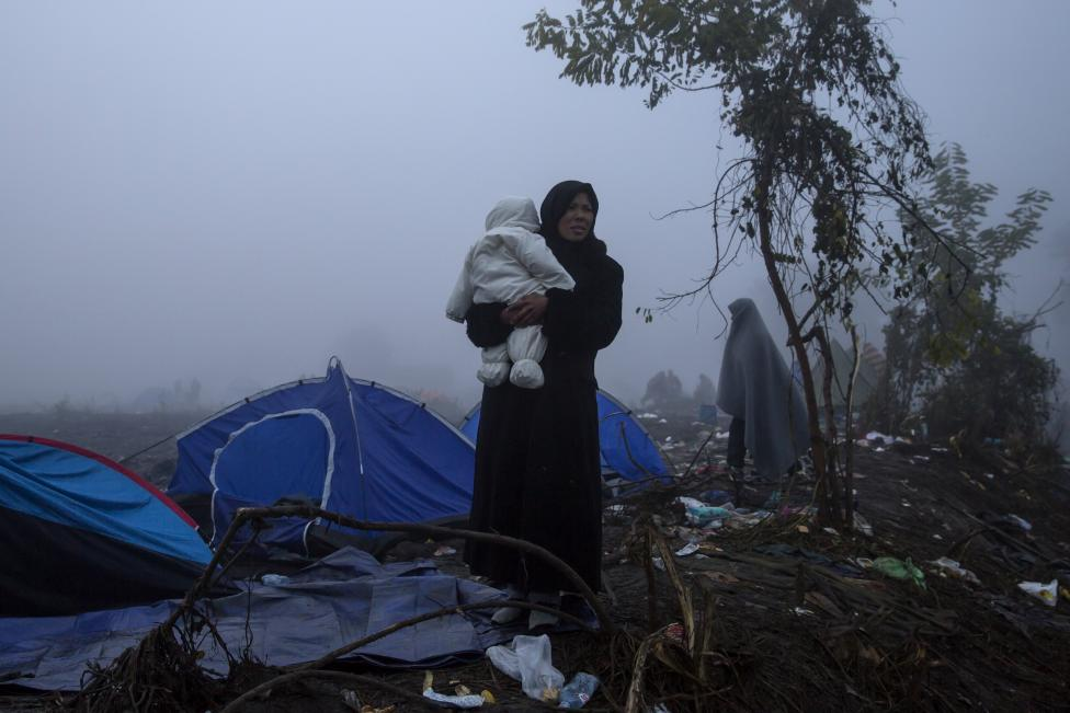 A migrant carries a child as she waits to cross the border with Croatia near the village of Berkasovo, Serbia, October 22, 2015. REUTERS/Marko Djurica