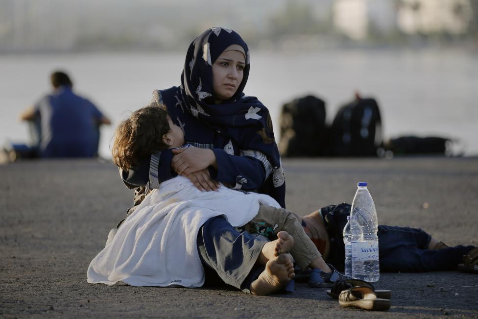 "A Syrian refugee holds her child in her arms as she sits in the port of the Greek island of Kos waiting to be registered and move with her family to the ""Eleftherios Venizelos"" vessel August 15, 2015. REUTERS/Yannis Behrakis"