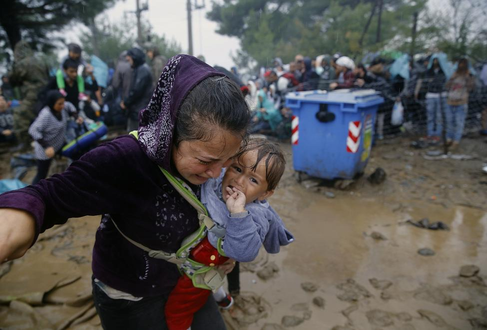 A Syrian refugee cries as she carries her baby walking through the mud to cross the border from Greece into Macedonia during a rainstorm, near the Greek village of Idomeni, September 10, 2015. REUTERS/Yannis Behrakis